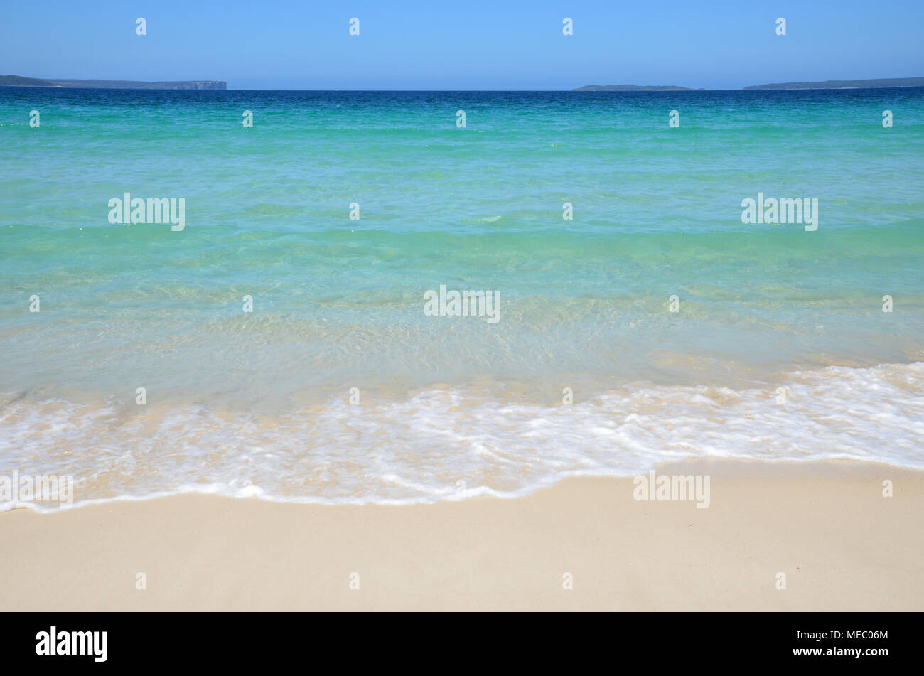 Scenic view from beach across bay to headland. Beach scene of ocean lapping on beach with calm water. - Stock Image