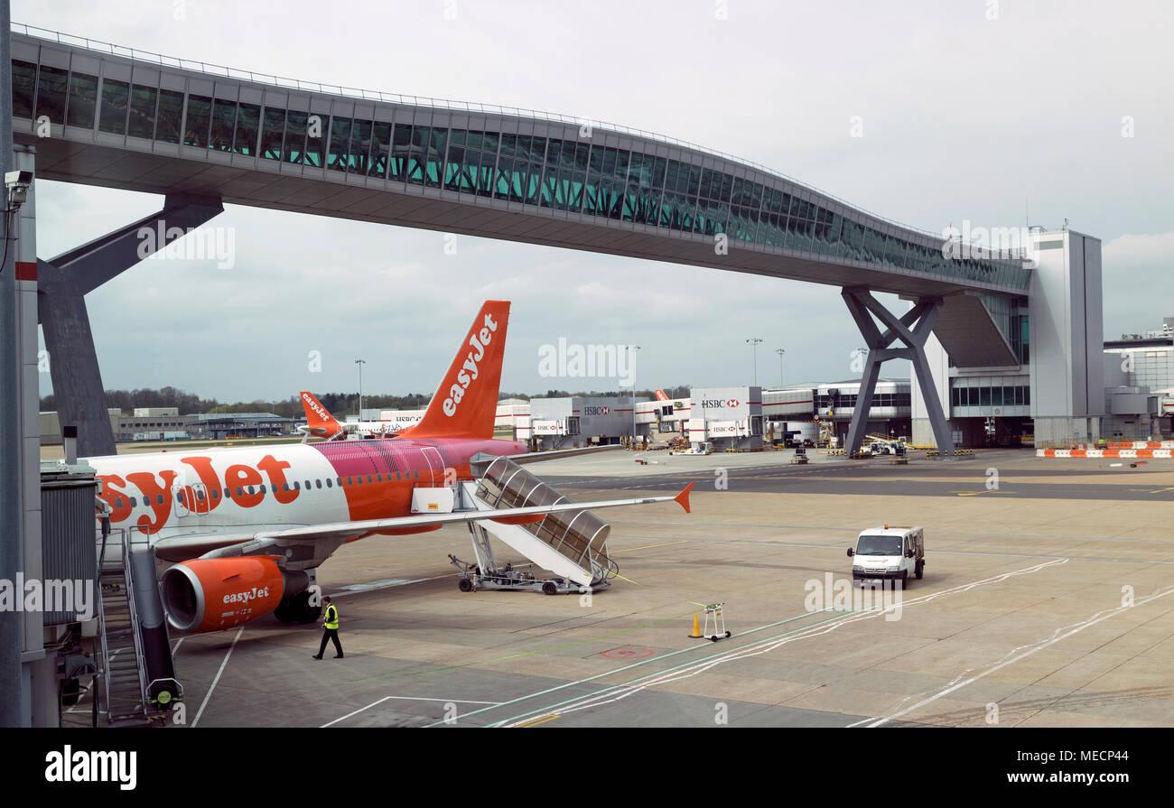London Gatwick Airport, Surrey, UK 2018. Passenger airbridge, planes pass below and passengers cross from terminals above groun - Stock Image