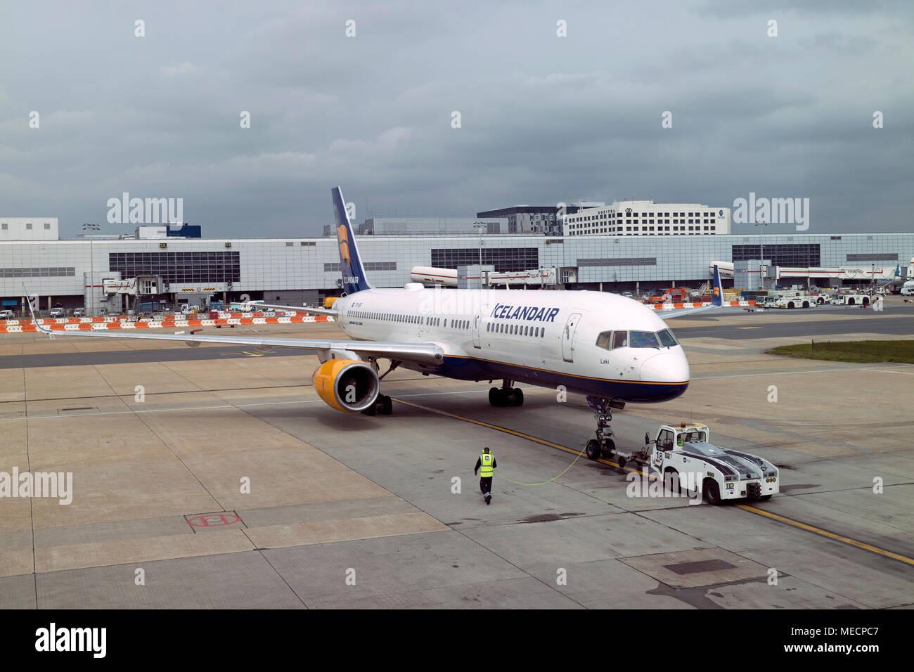 London Gatwick Airport, Surrey, UK 2018. Tug pushing a Icelandair Boeing 757-200 passenger jet to the taxiway - Stock Image