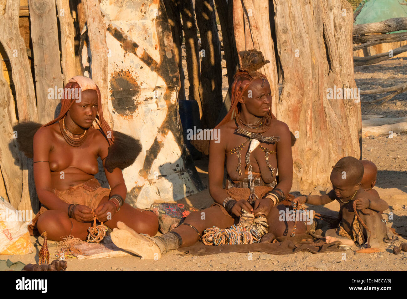 Himba people, Namibia- people siting near the huts in the village - Stock Image