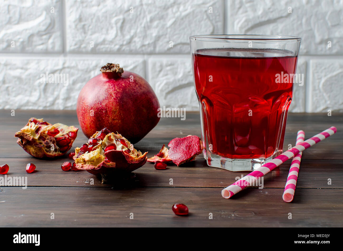 Fresh pomegranate juice in a glass with fruit pomegranates on a dark old wooden background Stock Photo