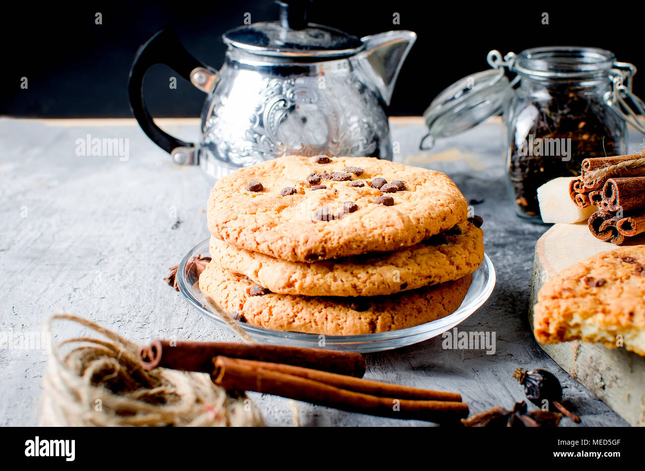 homemade cookies with chocolate drops, сup of hot black tea, cinnamon, anise on dark   background, spices for tea. - Stock Image