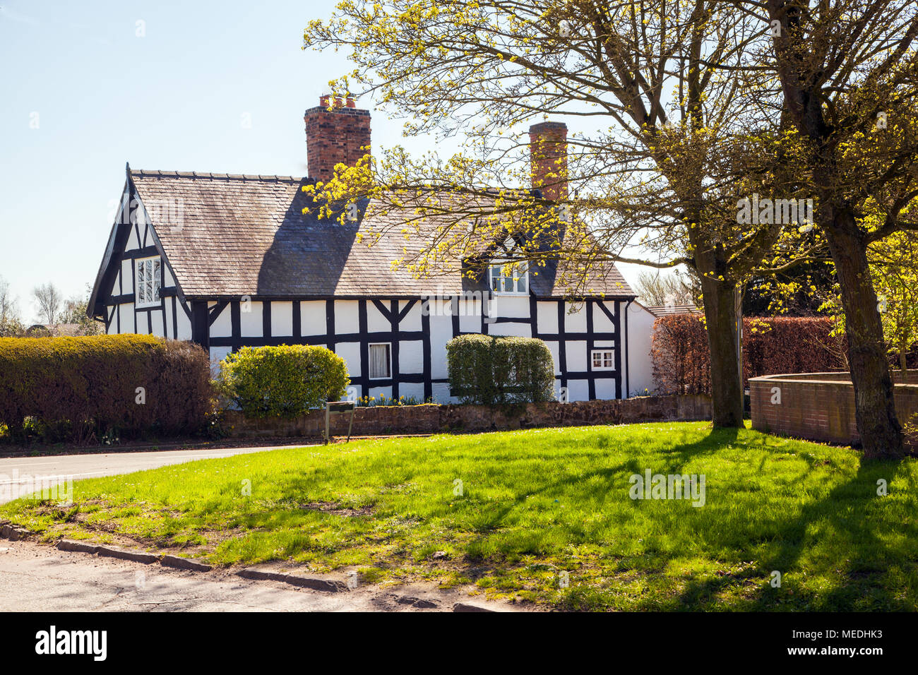 Black and white half timbered country cottage off the village green in the Cheshire village of Wrenbury in springtime - Stock Image