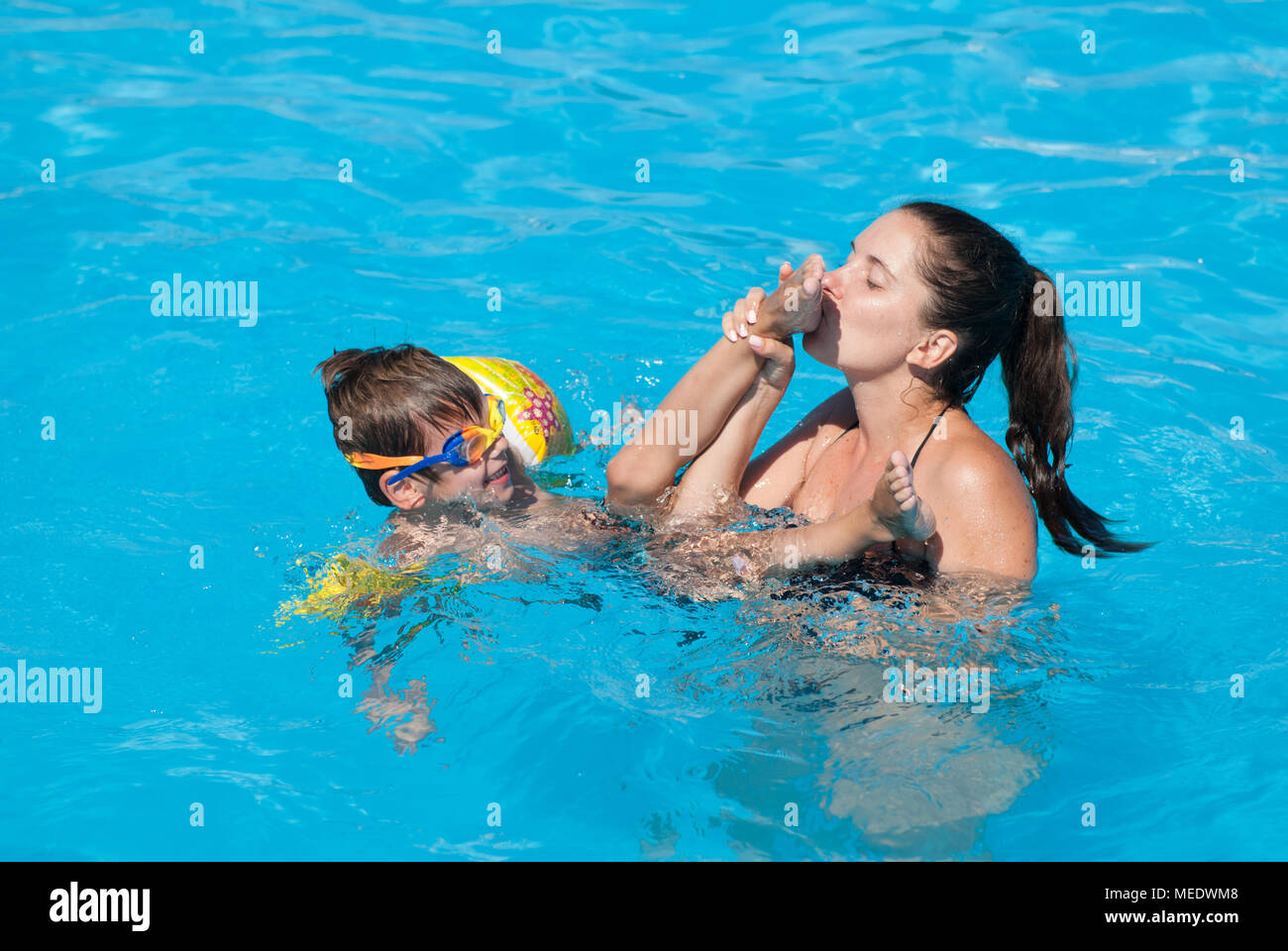 mother kisses foot of child swimming in blue pool on summer vacation Stock Photo