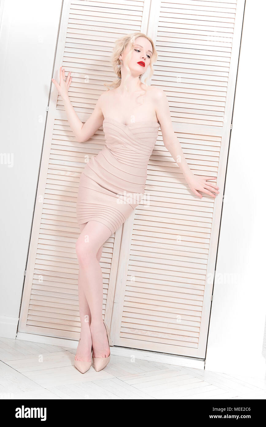 Elegant female model in a mini dress standing on a beige background and sensually poses. - Stock Image