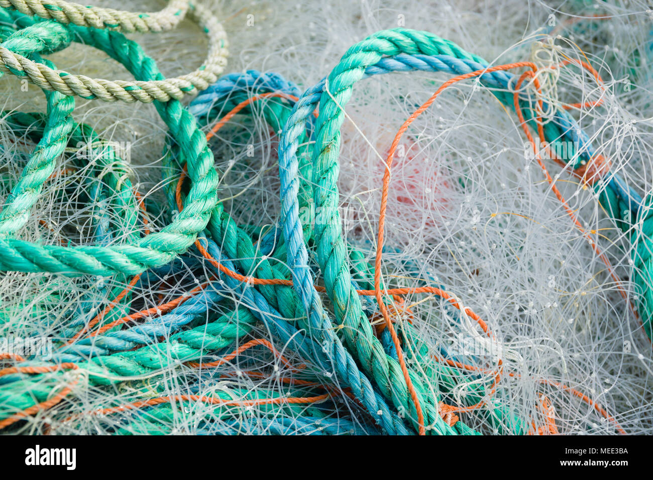 A tangled mess of fishing nets plastic rope and other debris washed up on a Cornish beach ideal for an ecological hazard or pollution concept - Stock Image