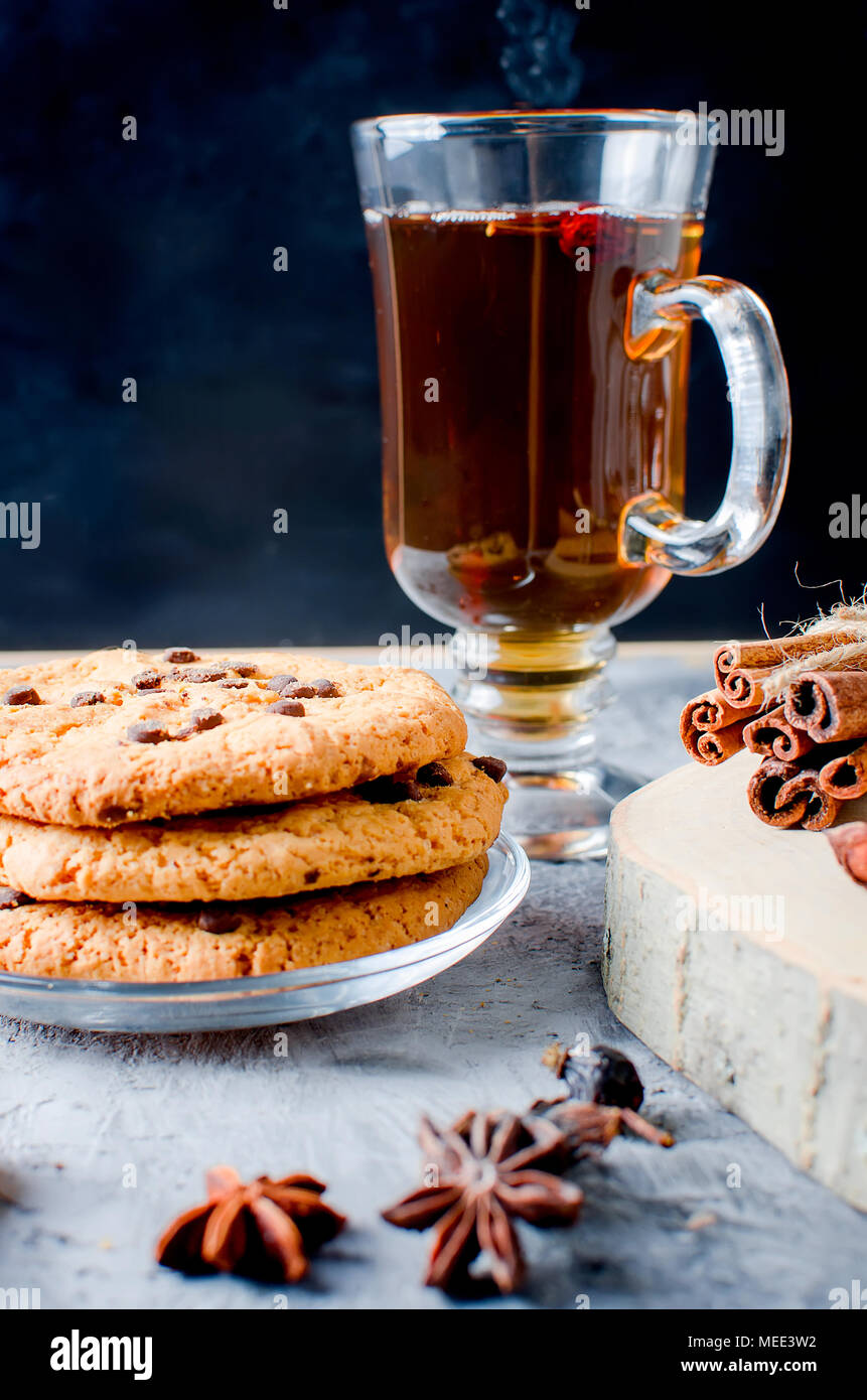 stack of homemade cookies with chocolate drops, сup of hot black tea, cinnamon, anise on dark   background, spices for tea. - Stock Image