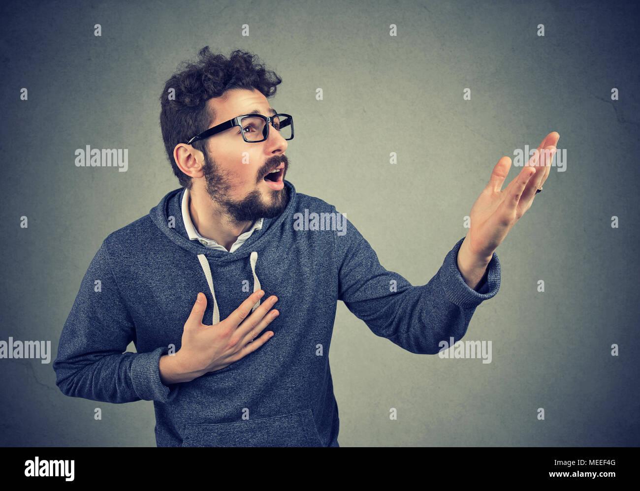 Desperate beard man screaming asking for help forgiveness - Stock Image