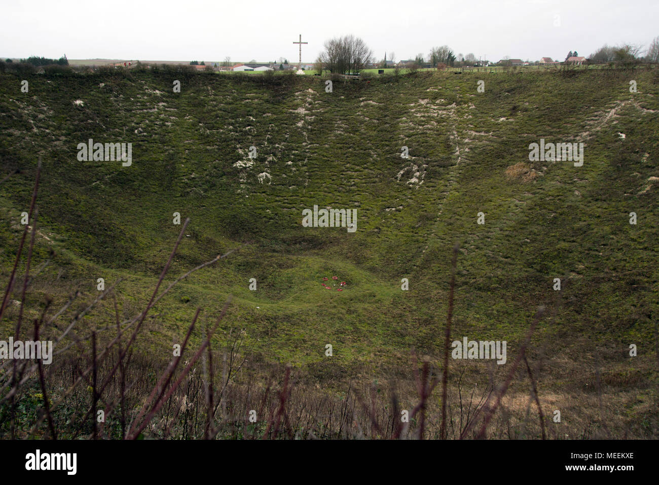 Lochnagar Crater, Ovillers, France showing massive hole with a cross in the background on the horizon - Stock Image