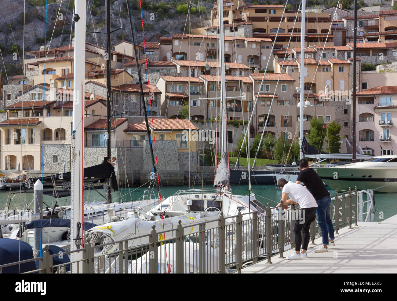 DUINO AURISINA, Italy - April 14, 2018: Two boys leant against a railing at the marina in Portopicclo, near Trieste, Italy - Stock Image