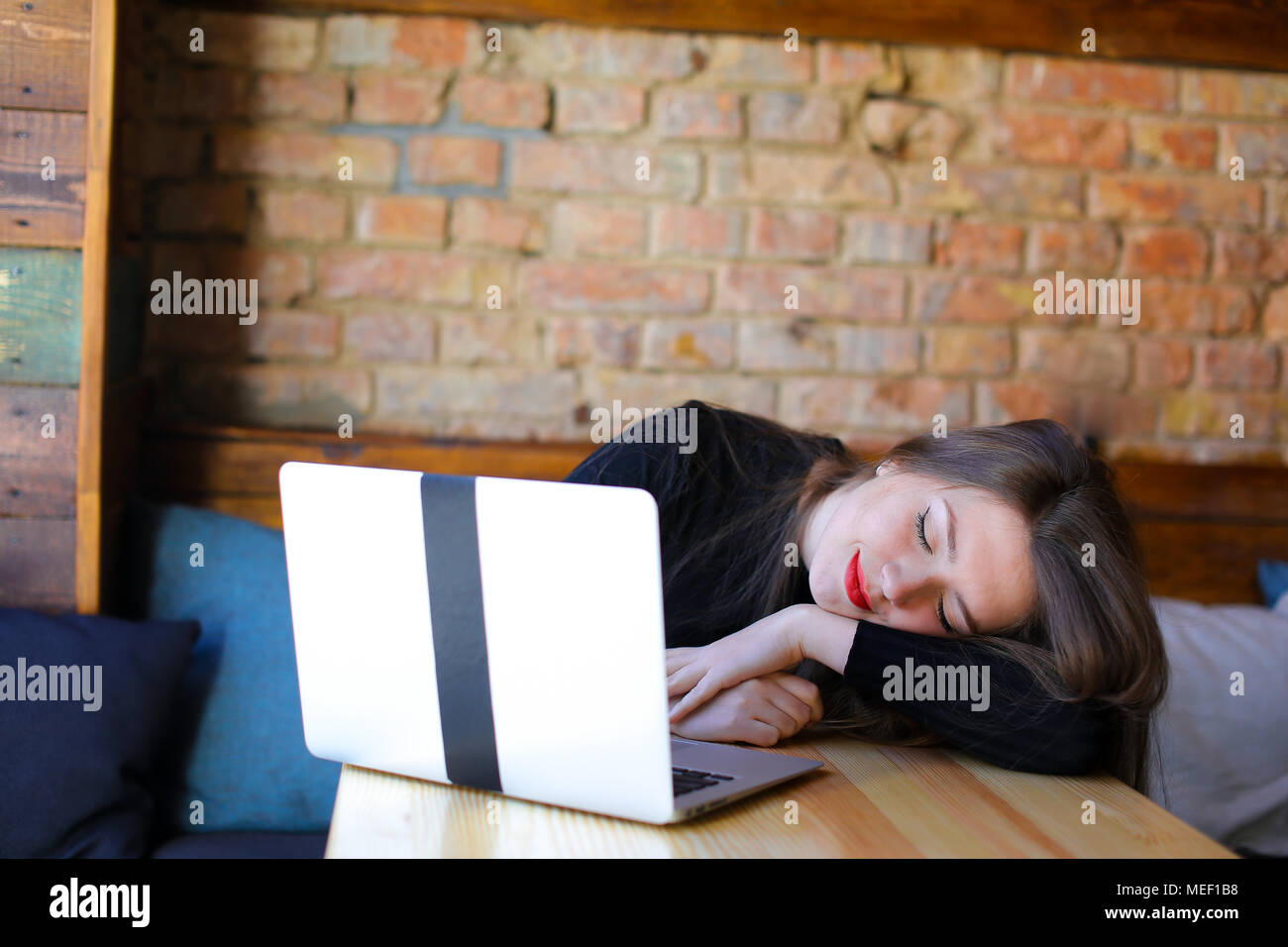 Tired student sleeping and sitting near modern laptop at cafe on sofa. - Stock Image