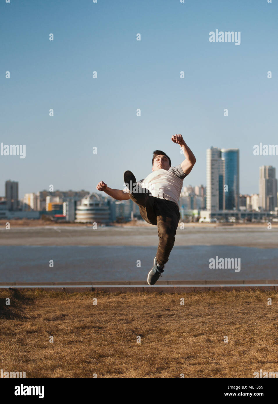 Young male parkour sportsman performs acrobatic jumps in front of skyline - Stock Image