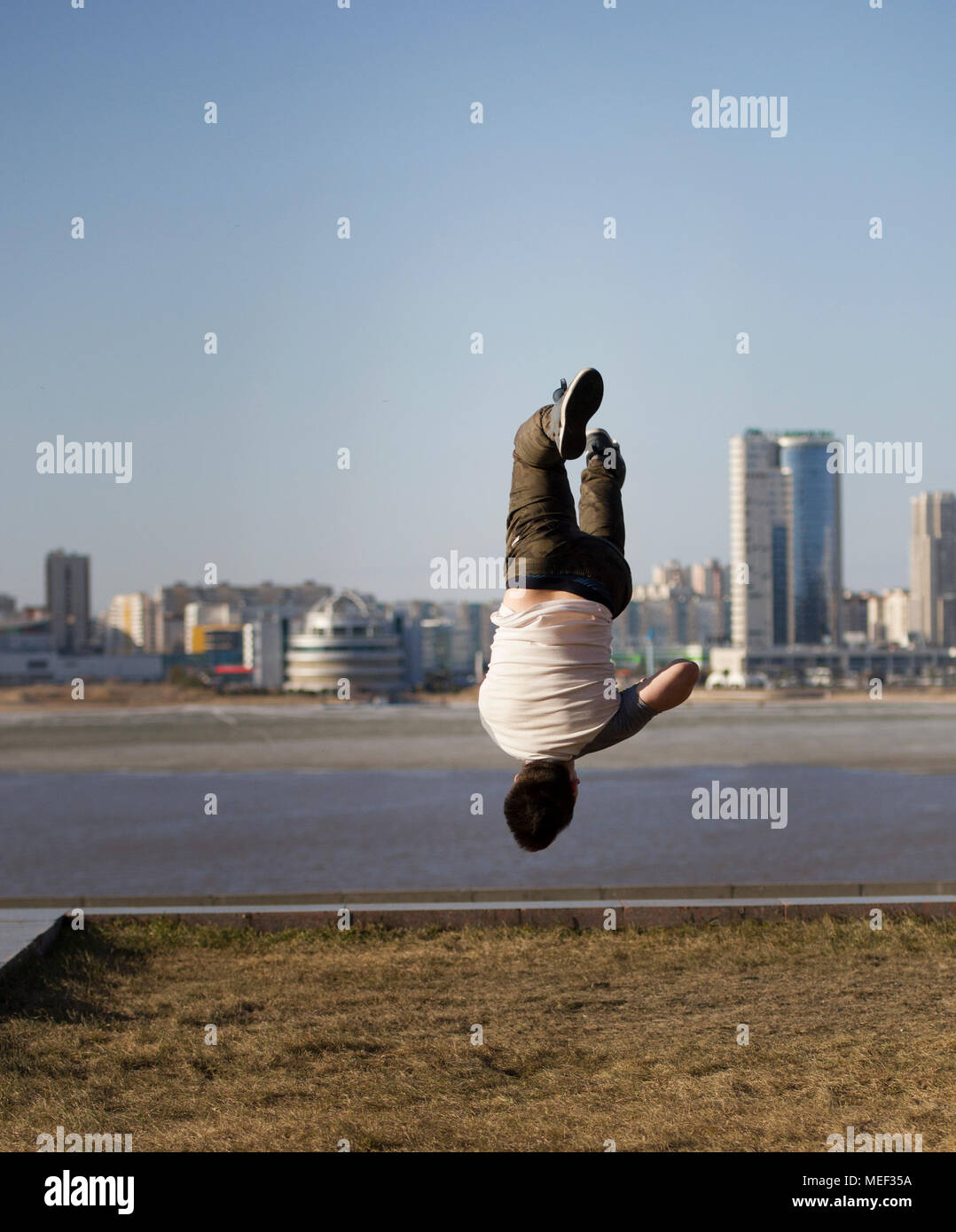 Young male acrobatic sportsman performs tricks upside down in front of skyline - Stock Image