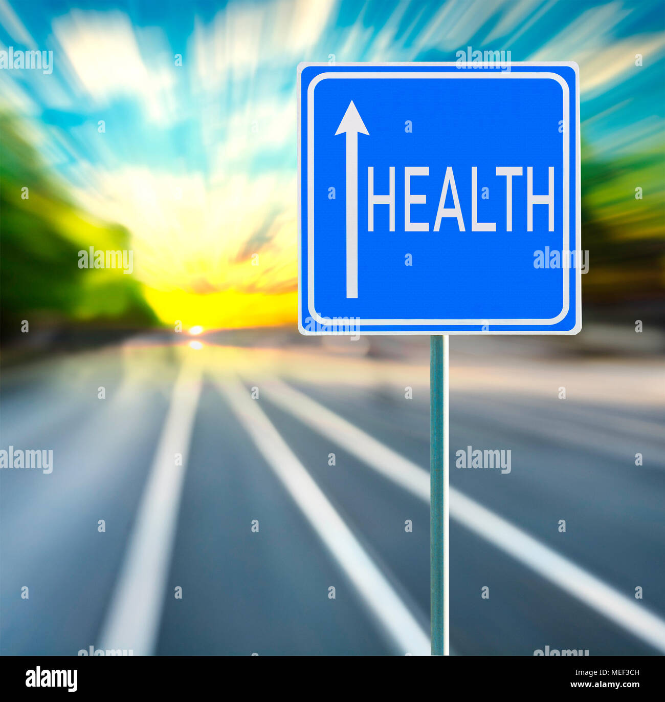 Health motivational phrase on blue road sign with arrow and blurred speedy background in sunset. Copy space. - Stock Image