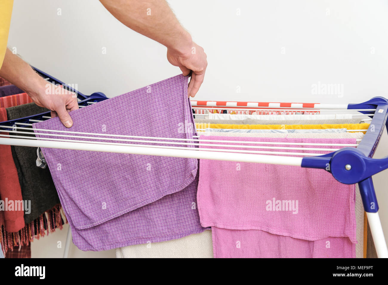 A man takes off towels from drying rack clothes. - Stock Image