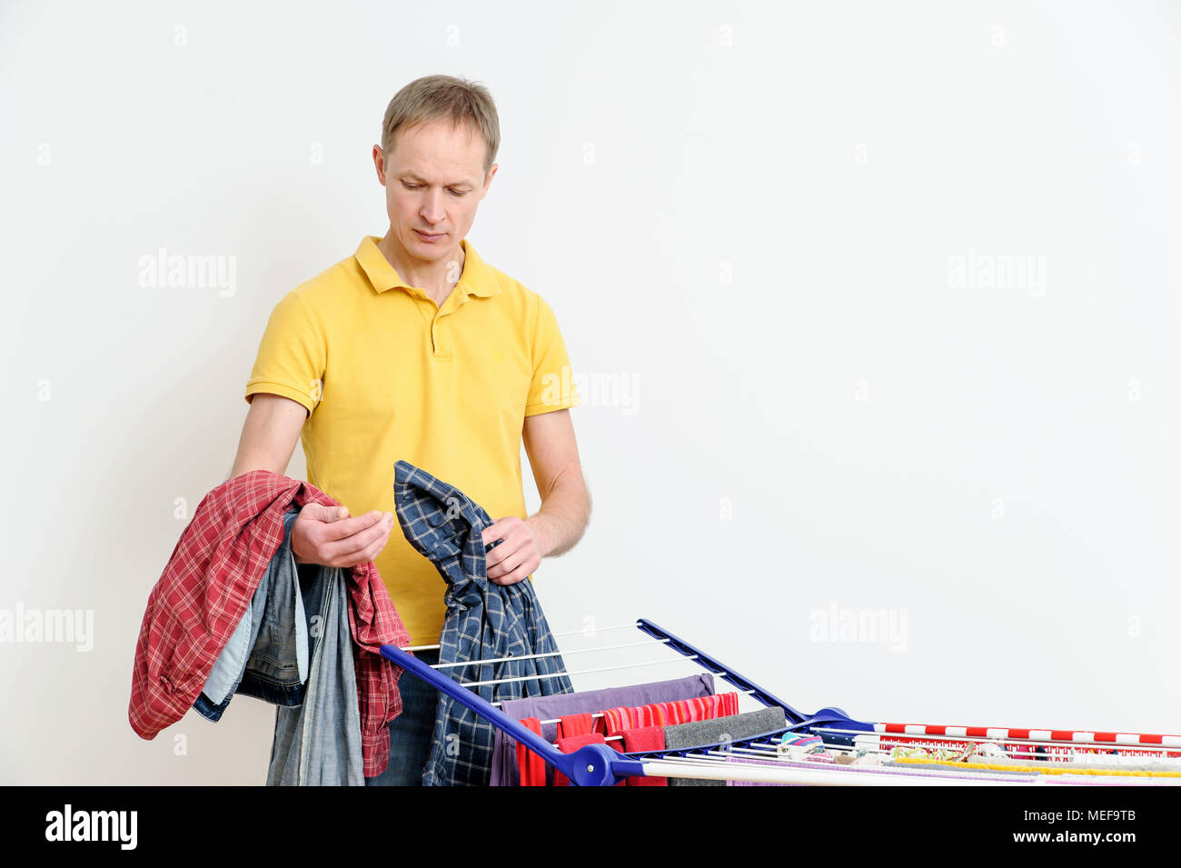 The man takes off things from drying rack clothes. - Stock Image