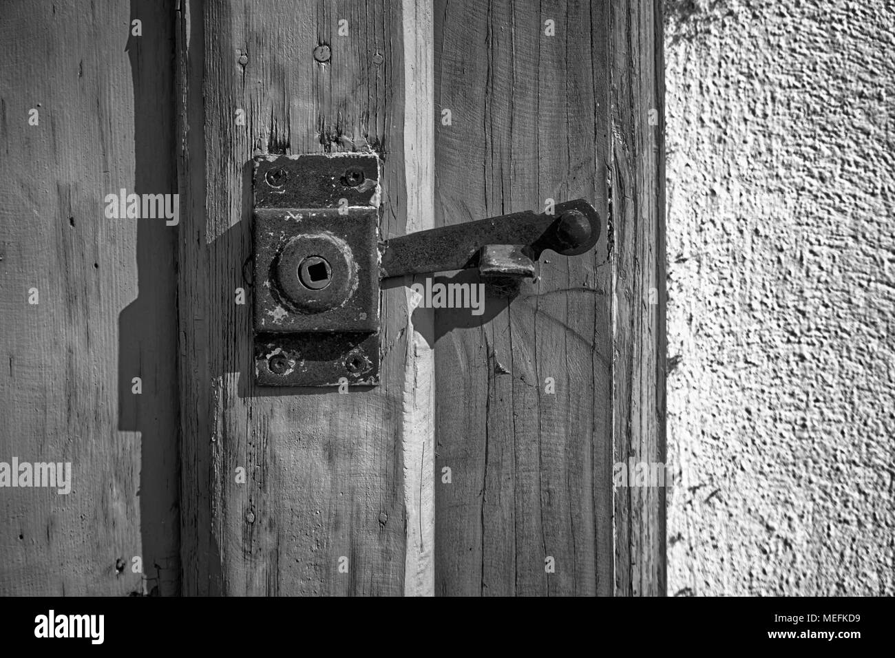 Rusty Ancient door latch, rough surface, sample for a postcard, security service. - Stock Image
