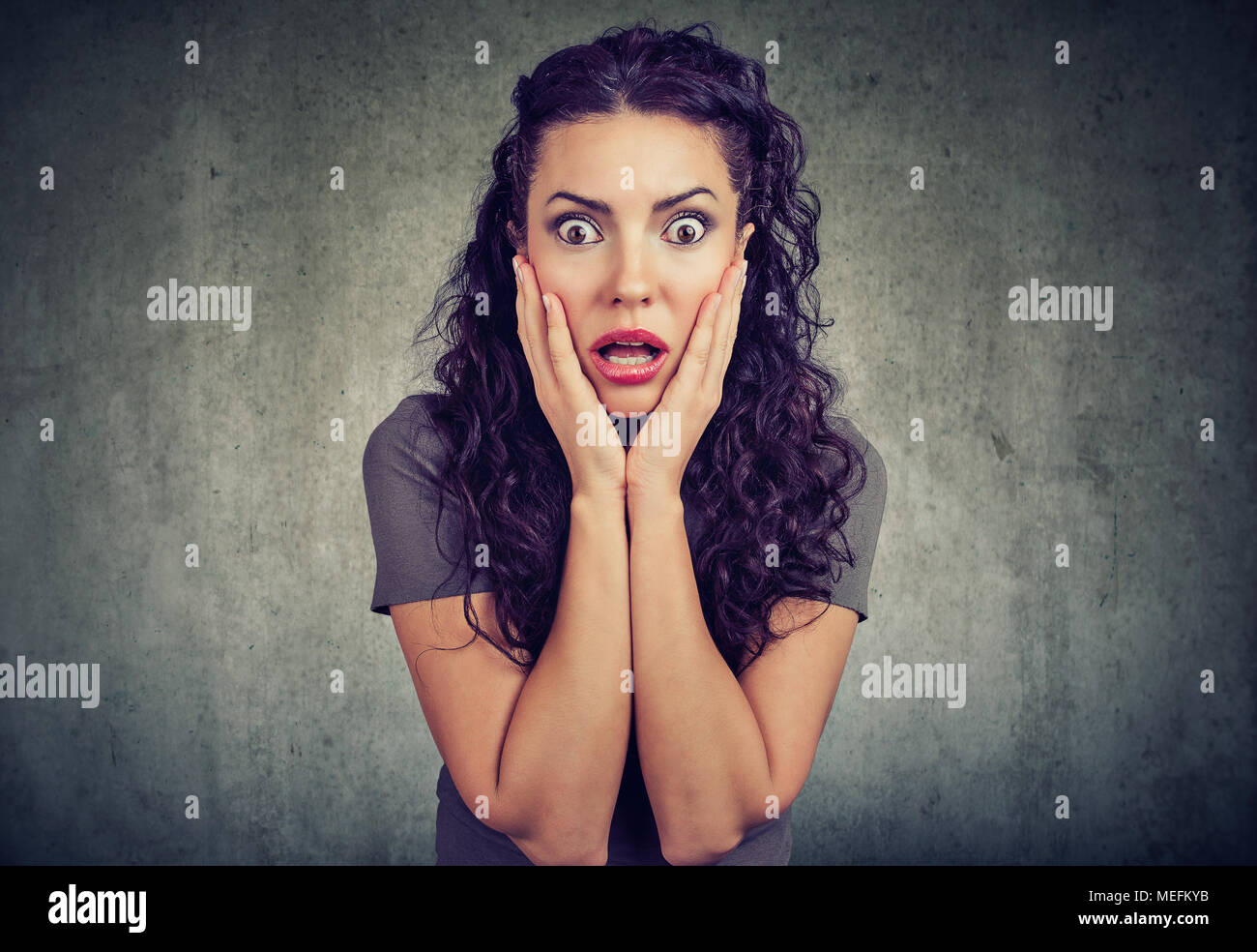 Amazed shocked woman looking at camera on gray wall background - Stock Image