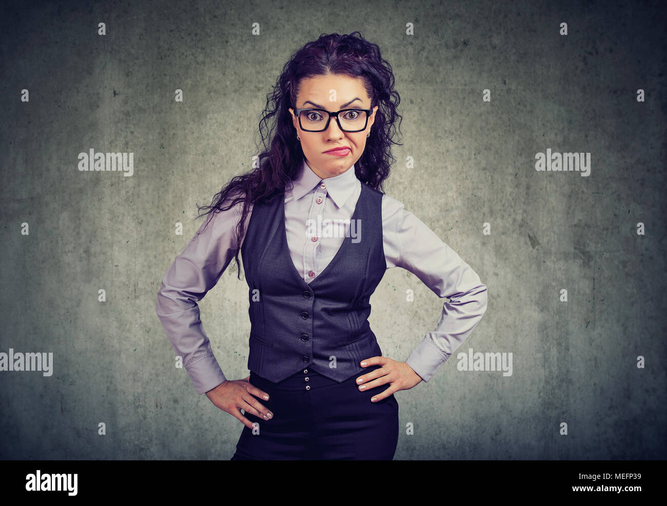 Woman in elegant suit and glasses looking at camera in disagreement holding hands on hips. - Stock Image