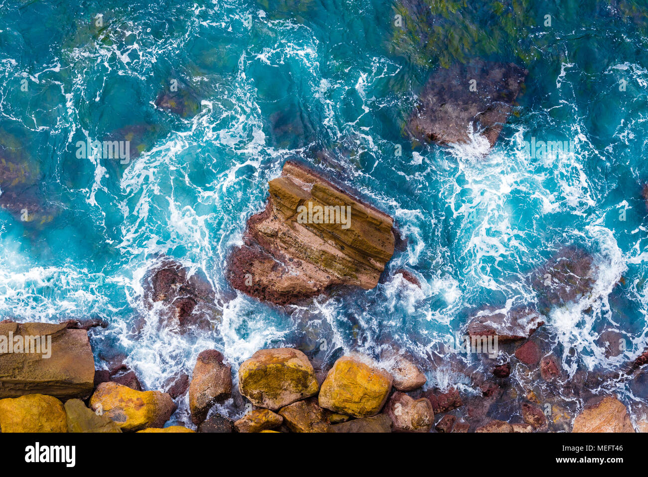 Top aerial view of blue waves crashing on rocky Australian coastline. Summer seascape with birds eye view shot over ocean waves and cliffs. Stock Photo