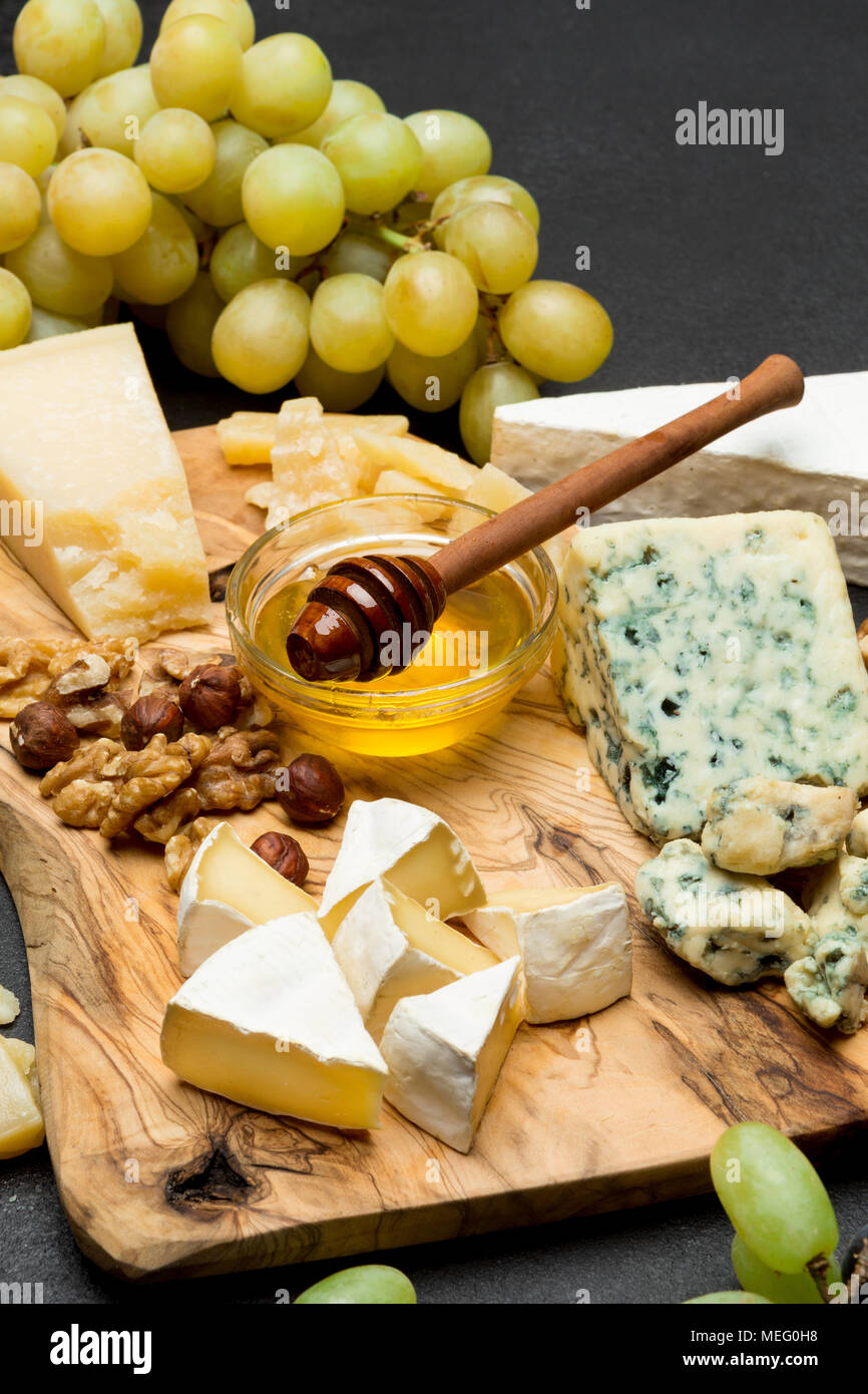 various types of cheese - brie, camembert, roquefort and cheddar and wine - Stock Image