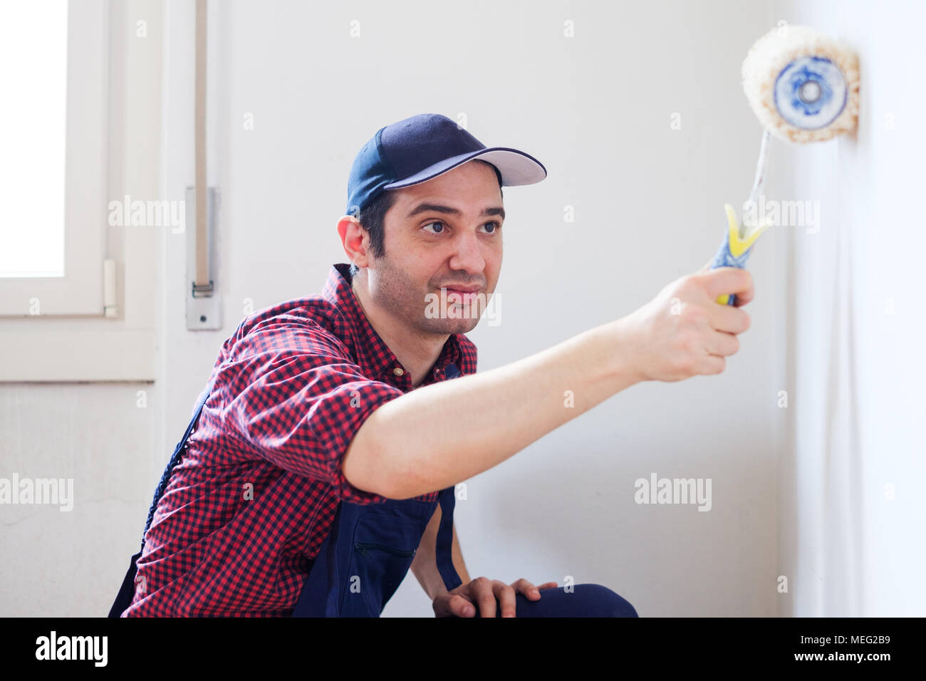 Painter man at work with a paint roller, home wall painting concept - Stock Image