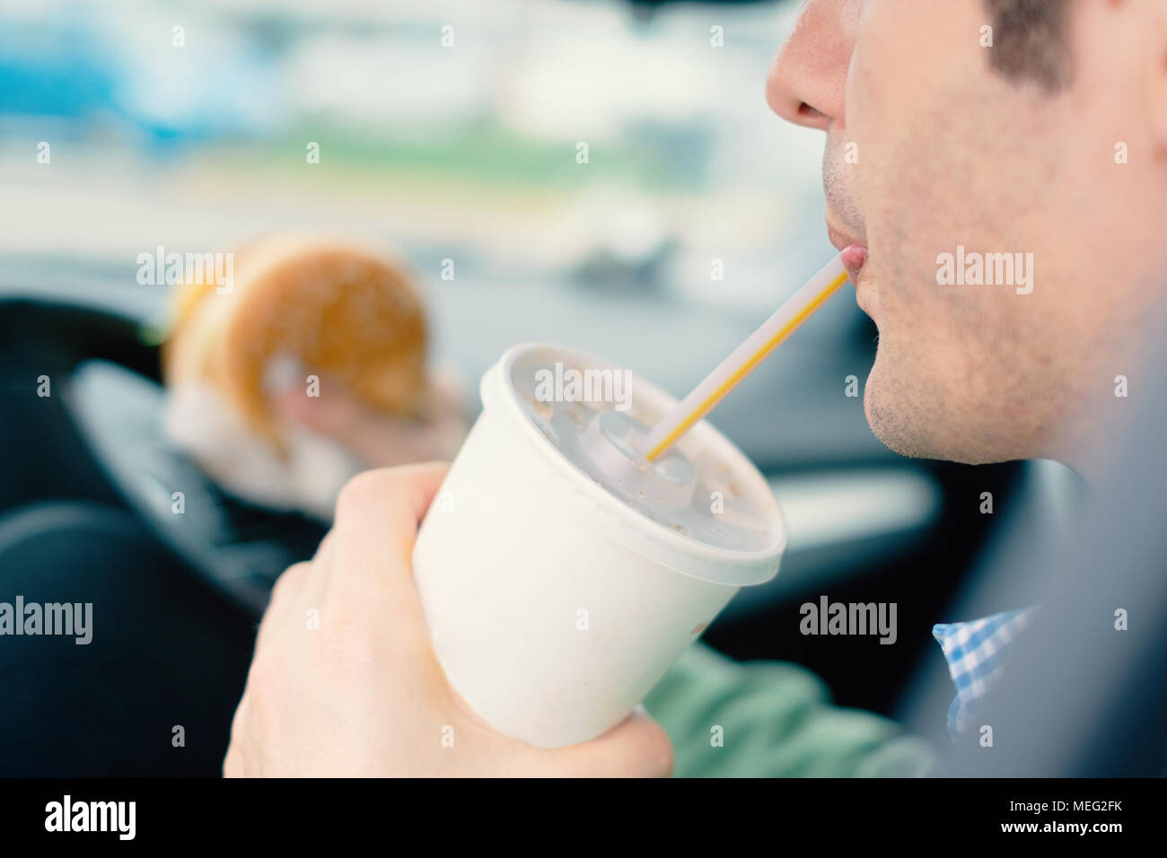 Man is dangerously eating junk food and cold drink while driving his car - Stock Image