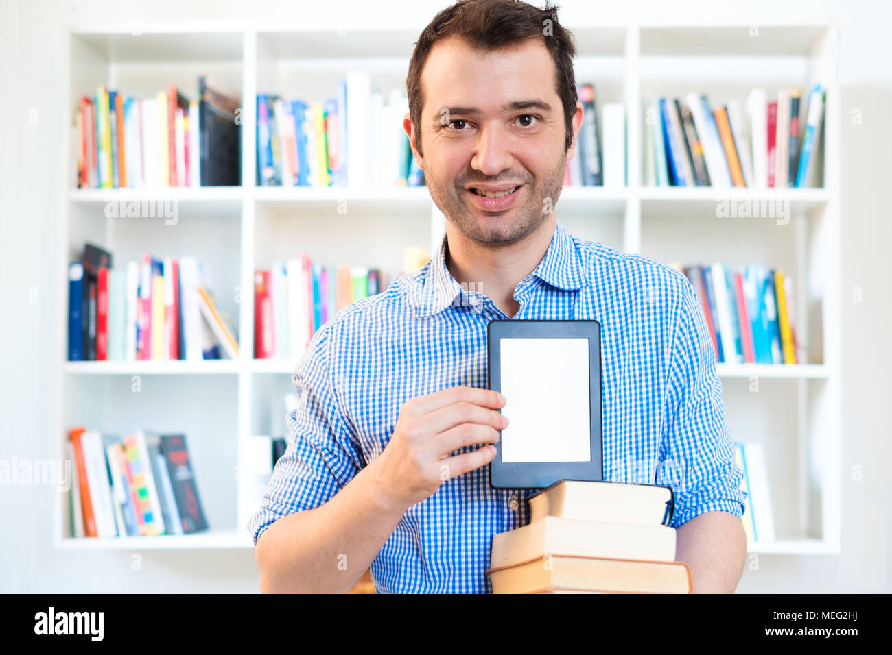 Man reading an e-book on digital tablet device - Stock Image