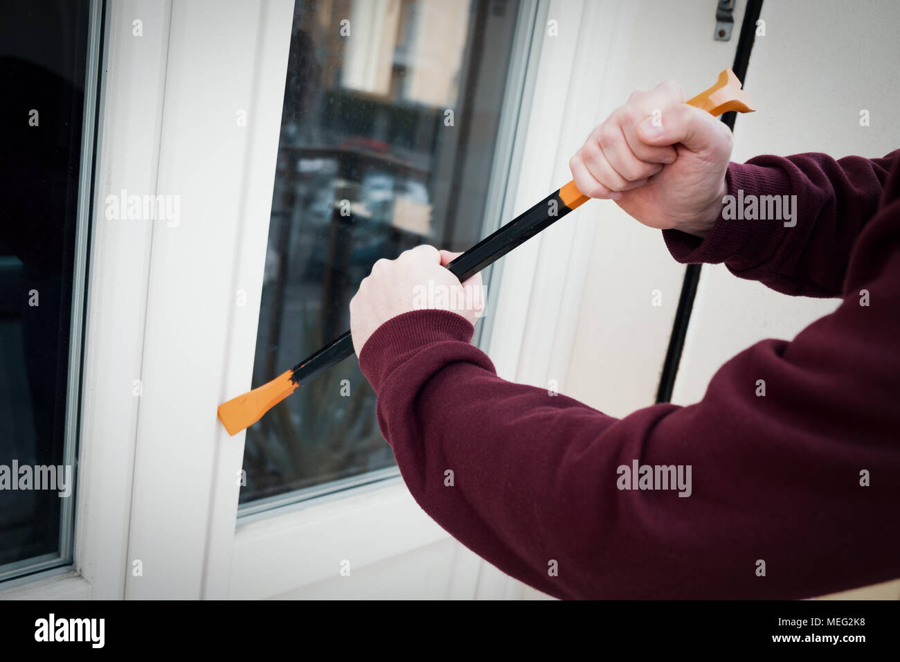Burglar forcing window to rob in the house Stock Photo