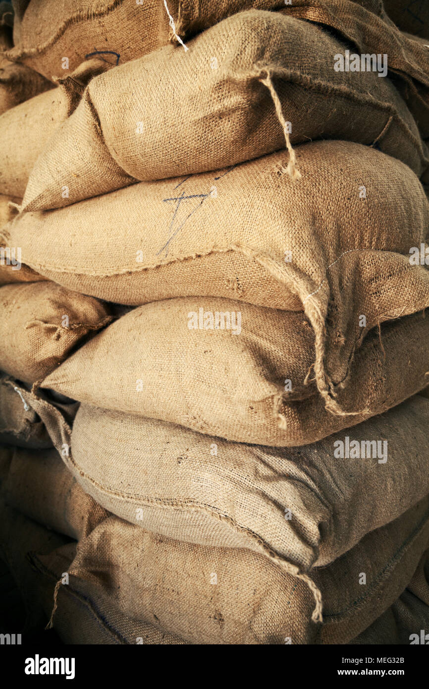 Stack of brown burlap sacks with grain at a warehouse. Big pile of hemp bags full of crop storing at a farm - Stock Image