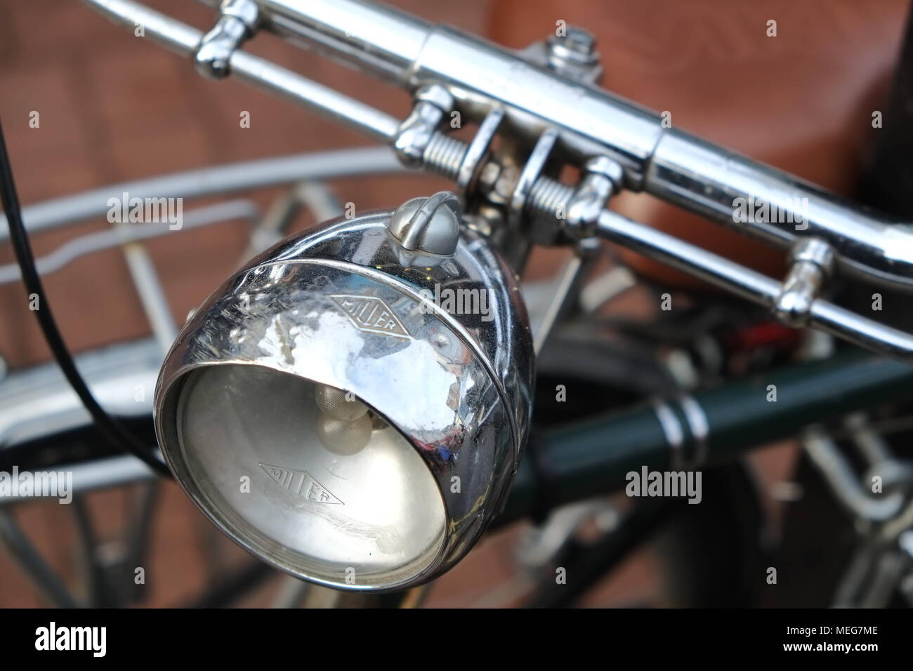 Vintage Bicycle detail showing headlamp with bike framework in the background. - Stock Image