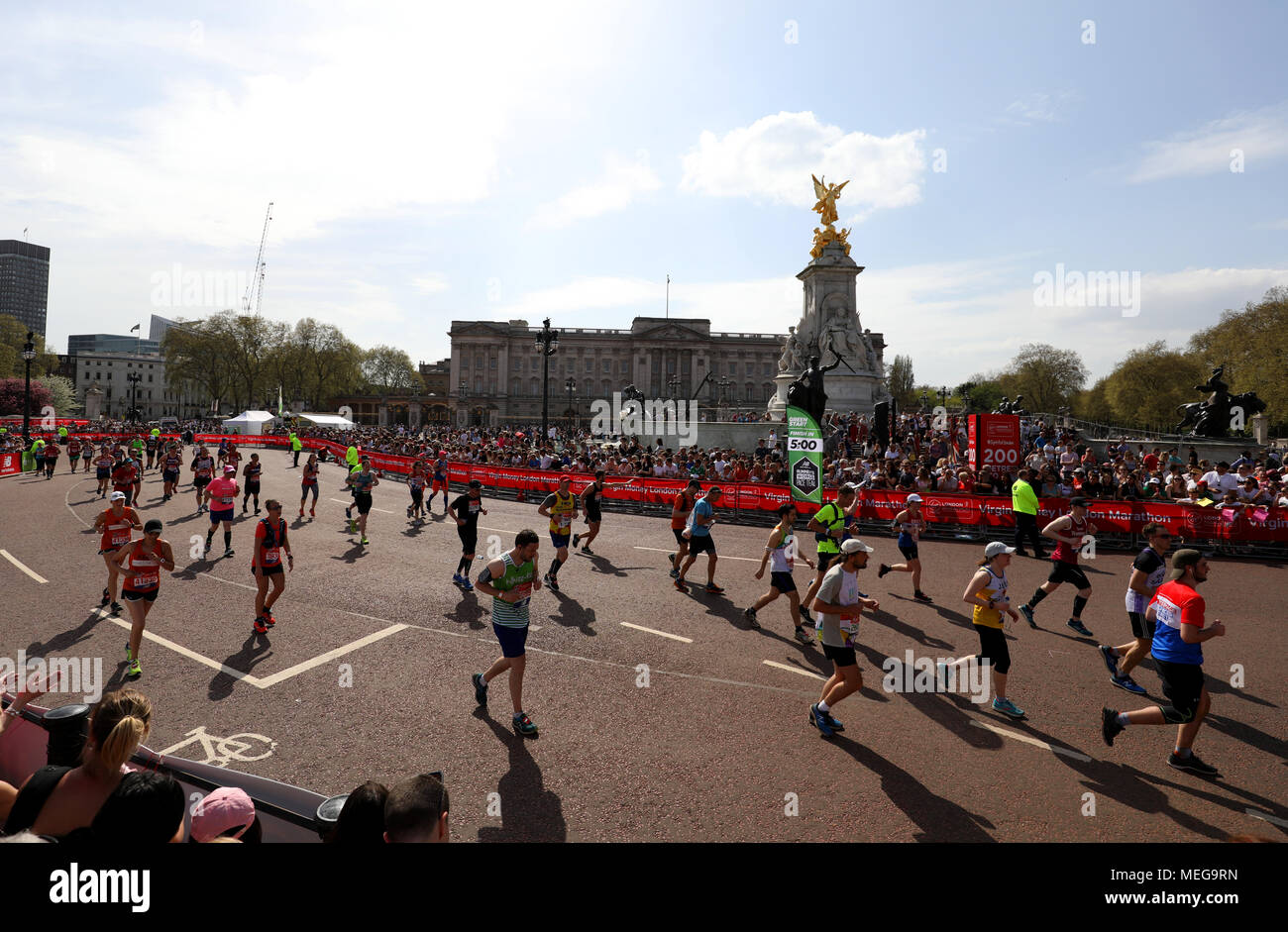 Runners go past Buckingham Palace during the 2018 Virgin Money London Marathon. - Stock Image