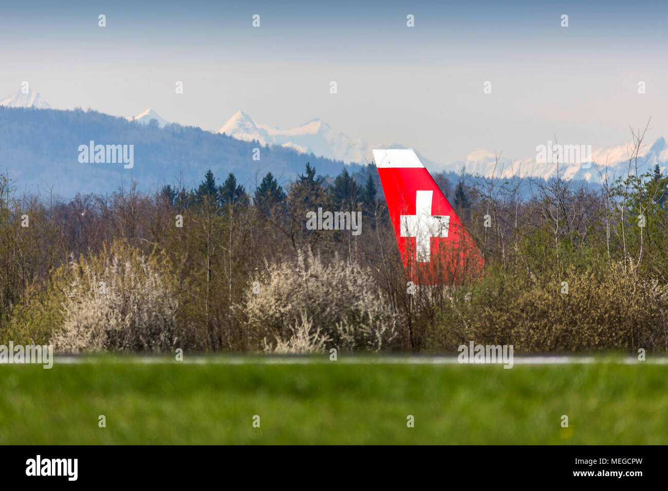 Airport Zuerich ZRH, Airplane taxiing to take-off position, tail fin of a Swiss airplane. Behind snow covered Alps. - Stock Image