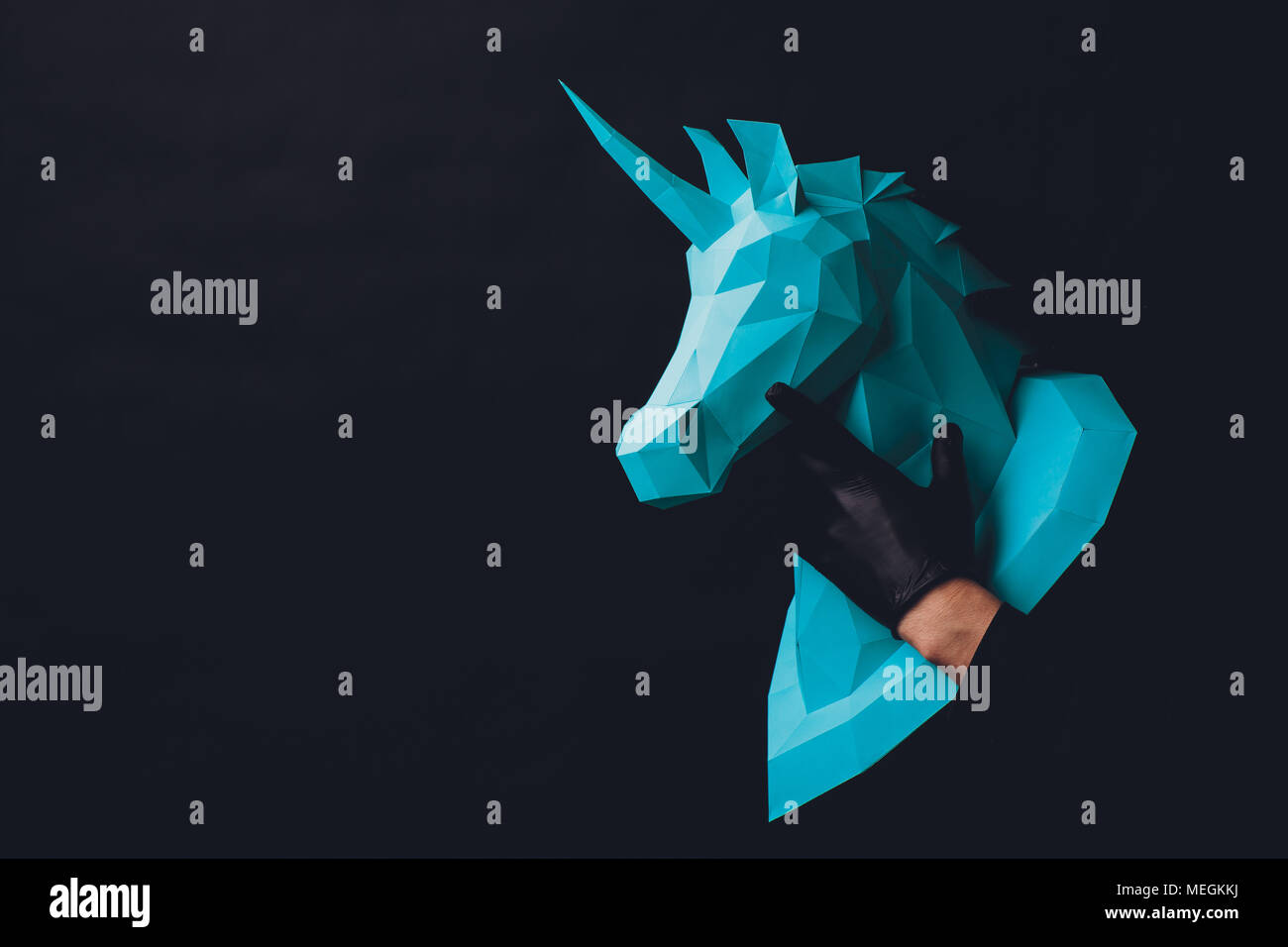 Unicorn head paper on a black background. Hands in black gloves hold a turquoise Unicorn. Copy space - Stock Image