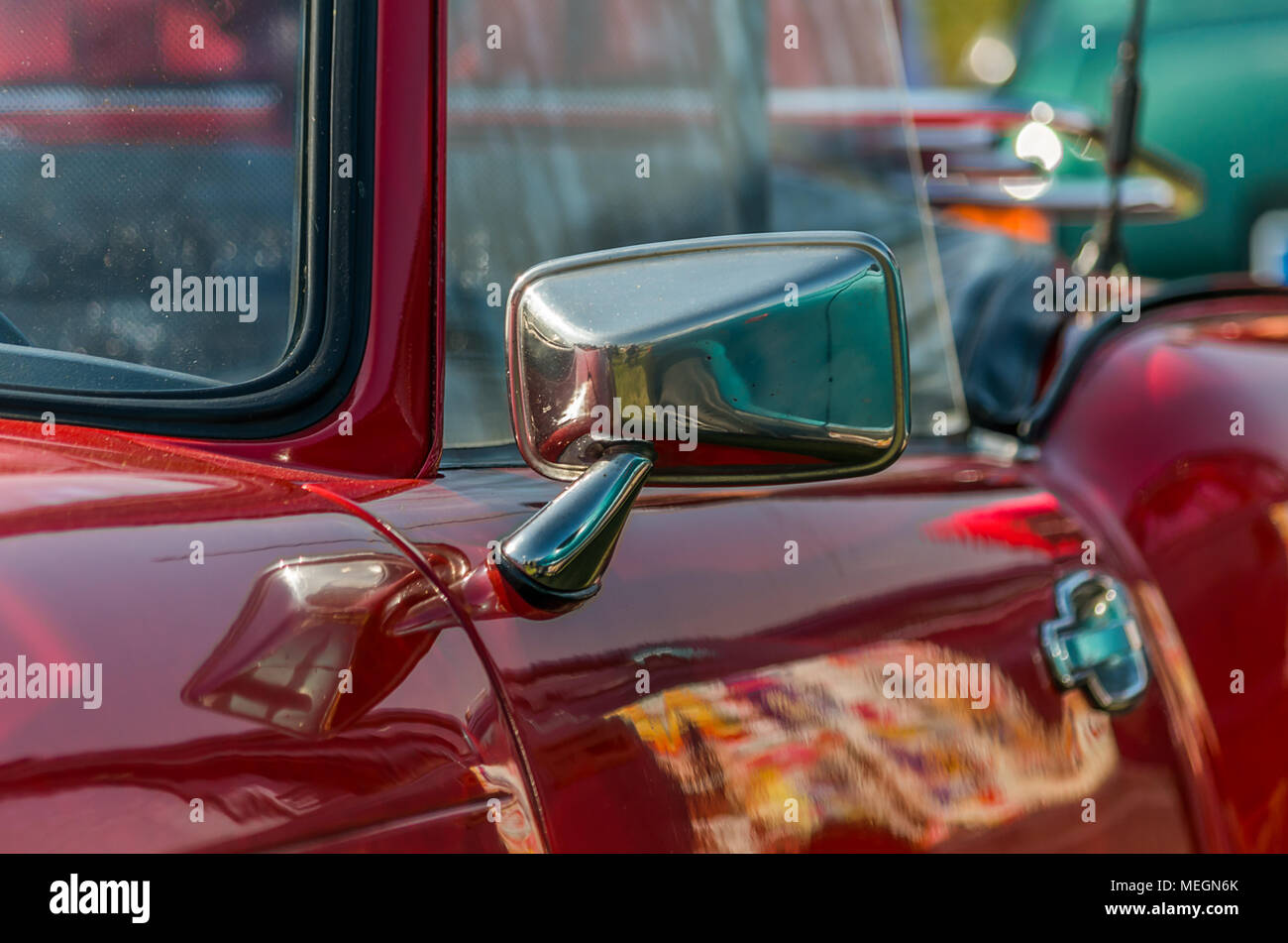 Red Triumph Spitfire vintage convertible car mirror closeup in Gliwice, Silesian Upland, Poland. - Stock Image