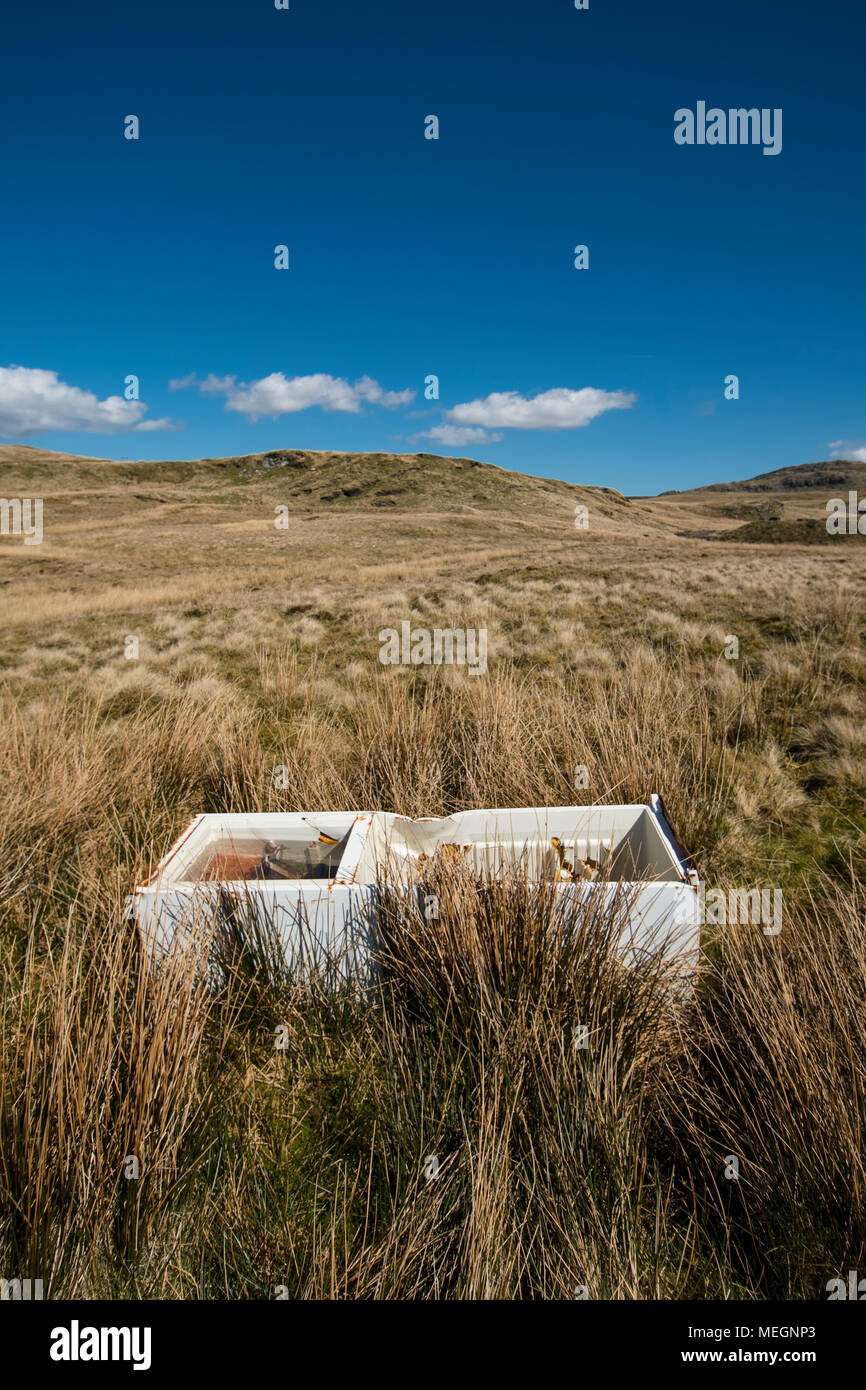 Fly tipped fridge freezer dumped on a moorland in North Wales. The fridge freezer dumped on y Migneint, an upland moor and peat bog and SSSI - Stock Image