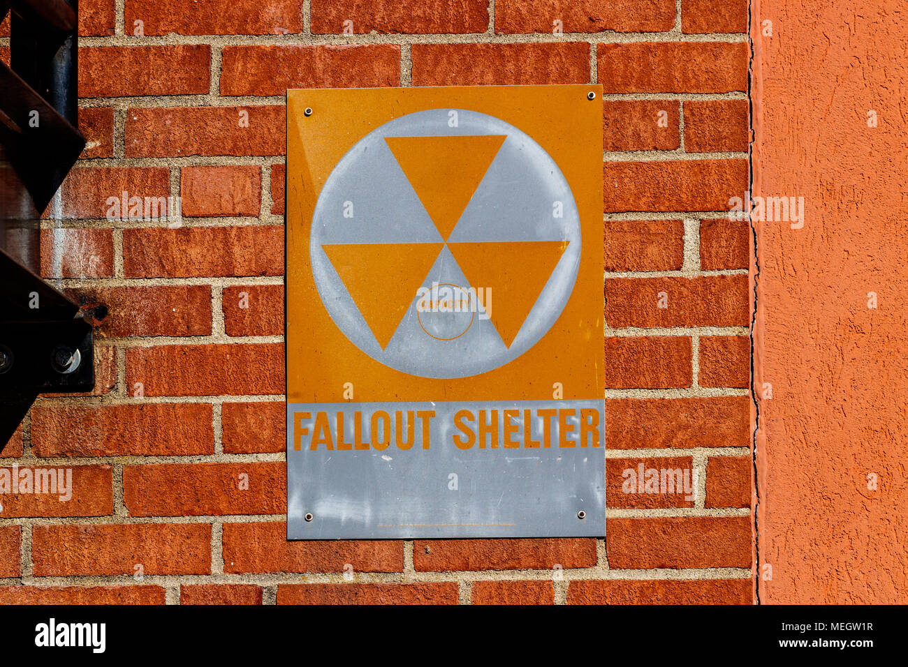 Orange 'Fallout Shelter' sign on a brick wall. With North Korea performing nuclear missile tests, Fallout Shelters may become more popular I - Stock Photo