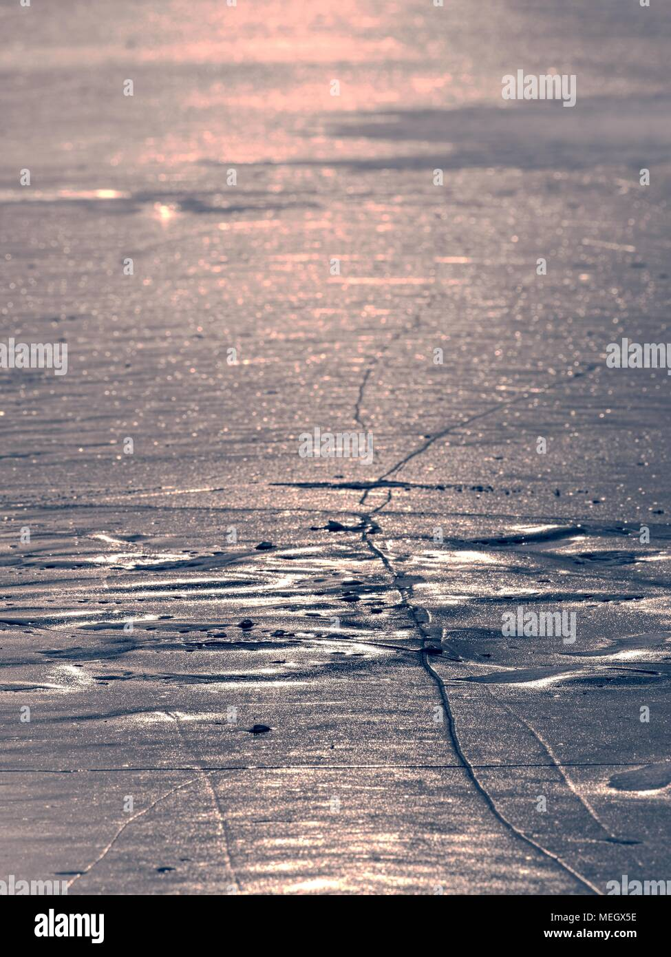 Shards of cracked ice jut out on the frozen lake. The light phenomenon occurs around a very specific time of year - Stock Image