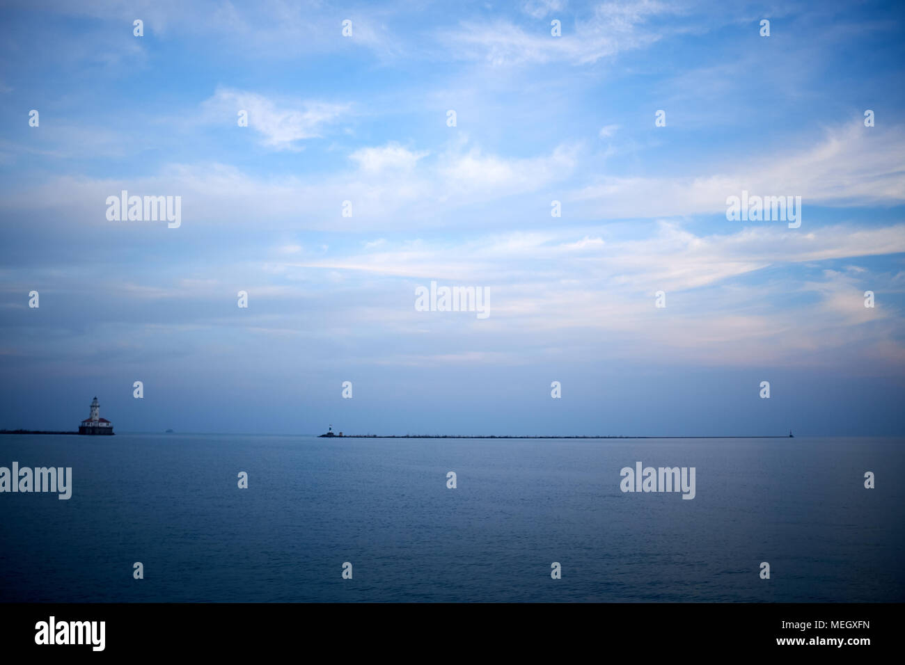 Minimalist blue toned water landscape on Lake Michigan with a distant pier and navigation beacon on the horizon and vignette Stock Photo