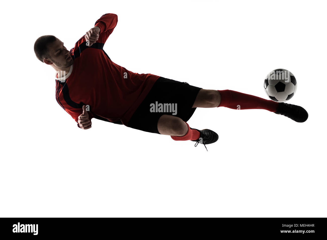 one caucasian soccer player man playing kicking in silhouette isolated on white background - Stock Image