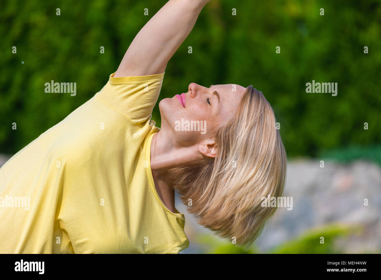 Beautiful pregnant woman doing prenatal yoga on nature. - Stock Image