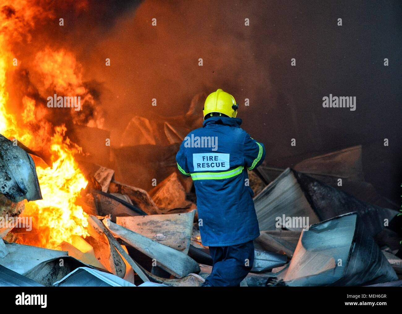 Firefighter battling with fire, fire rescue looking for survivor. Huge flames burned a recycling company in Tirana, fireman extinguishing the blaze - Stock Image