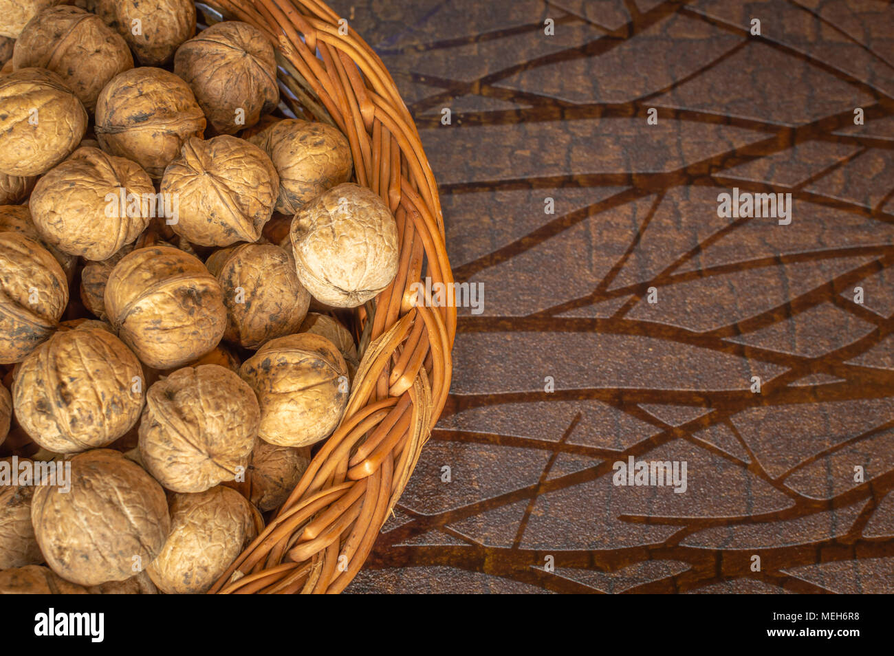 Walnuts in a wooden bowl on a wooden table walnuts with shells - Stock Image