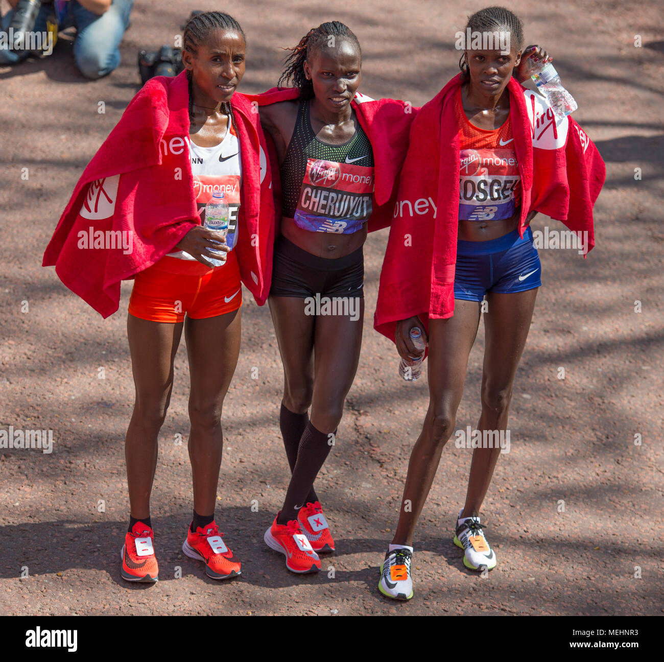 The Mall, London, UK. 22 April 2018. The Virgin Money London Marathon takes place in hot sun with athletes finishing on The Mall. Vivian Cheruiyot (KEN) wins the Elite Women's race, here with Brigid Kosgei (KEN) and Tadelech Bekele (ETH). Credit: Malcolm Park/Alamy Live News. Stock Photo