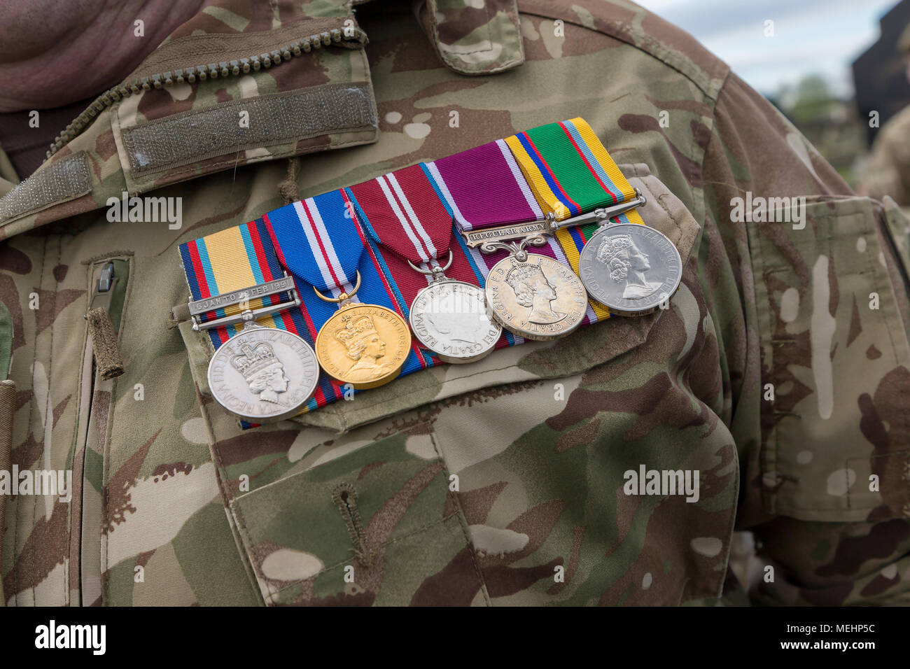 Warrington, UK, 22 April 2018. Medals worn on the chest of a Senior Officer from The Queen's Lancashire Regiment in camouflage kit on ANZAC day in Soldiers' Corner of Warrington Cemetery on Sunday 22 April 2018 Credit: John Hopkins/Alamy Live News - Stock Image