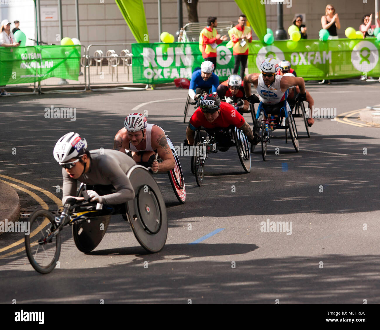 The Elite Mens Wheelchair Athletes pass through  Cabot Square, Canary Wharf, at 18 miles during the 2018 London marathon. David  Wier (Black helmet) went on to  win the men's wheelchair race in a time of 01.31.15. - Stock Image