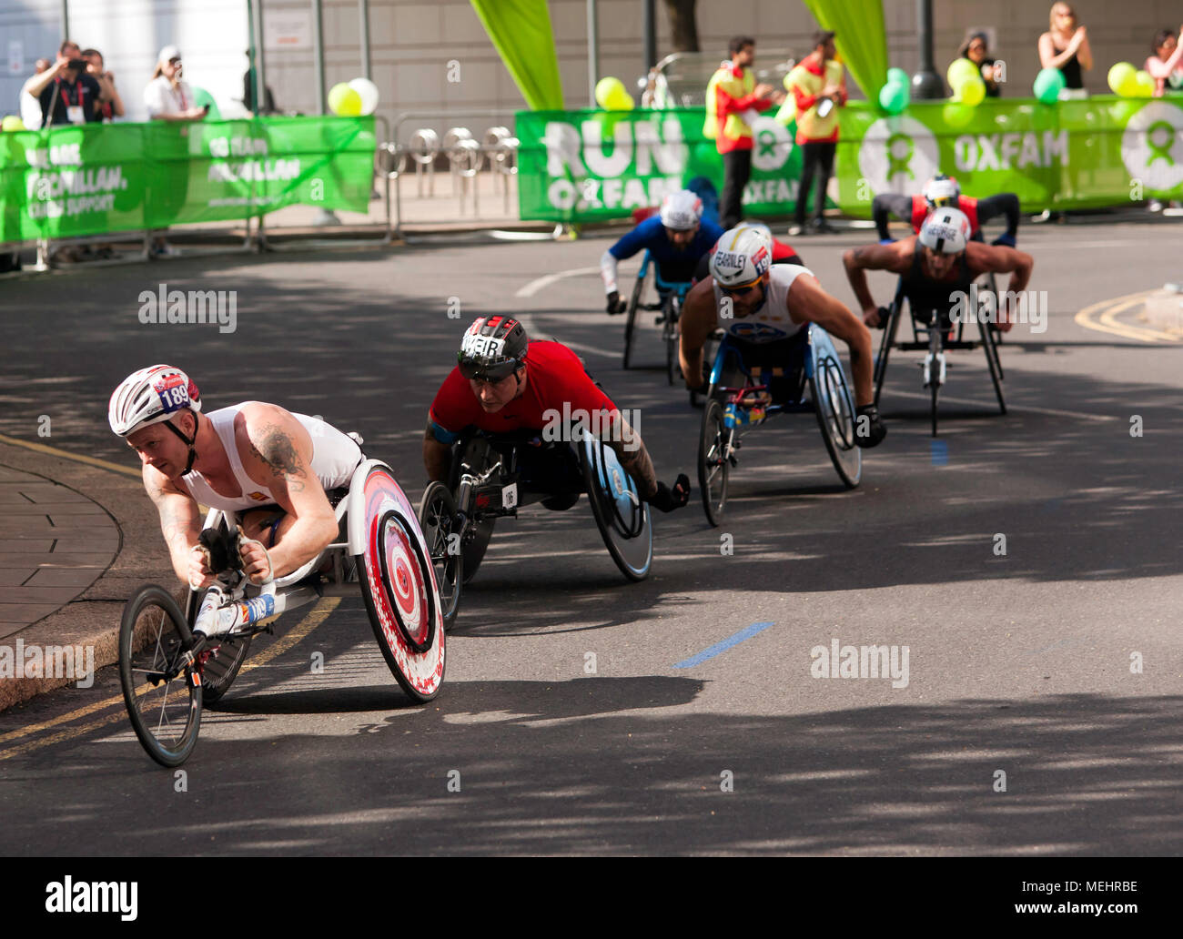 The Elite Mens Wheelchair Athletes pass through  Cabot Square, Canary Wharf, at 18 miles during the 2018 London matrathon. David  Wier (Black helmet) went on to  win the mens wheelchauir race in a time of 01.31.15. - Stock Image