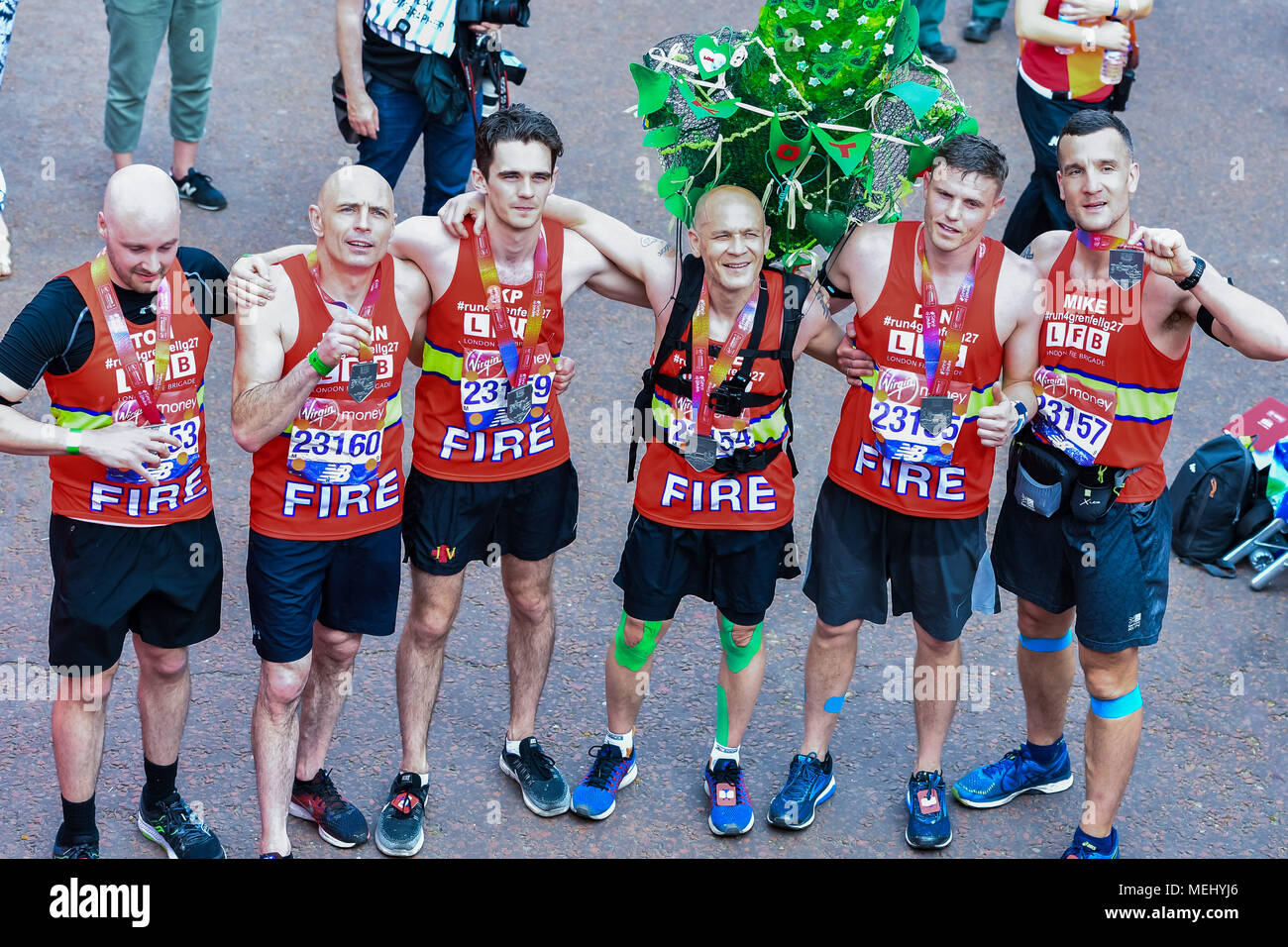 London, UK, 22 April 2018: The Firefight Team (from left) - Tom Abell, Justin O'Beirne, Michael Krikpatick, Dave Badillo, Dan Bills and Mike Dowden at the finish line during the 2018 Virgin Money London Marathon on Sunday, 22 April 2018. London, England. Credit: Taka G Wu - Stock Image