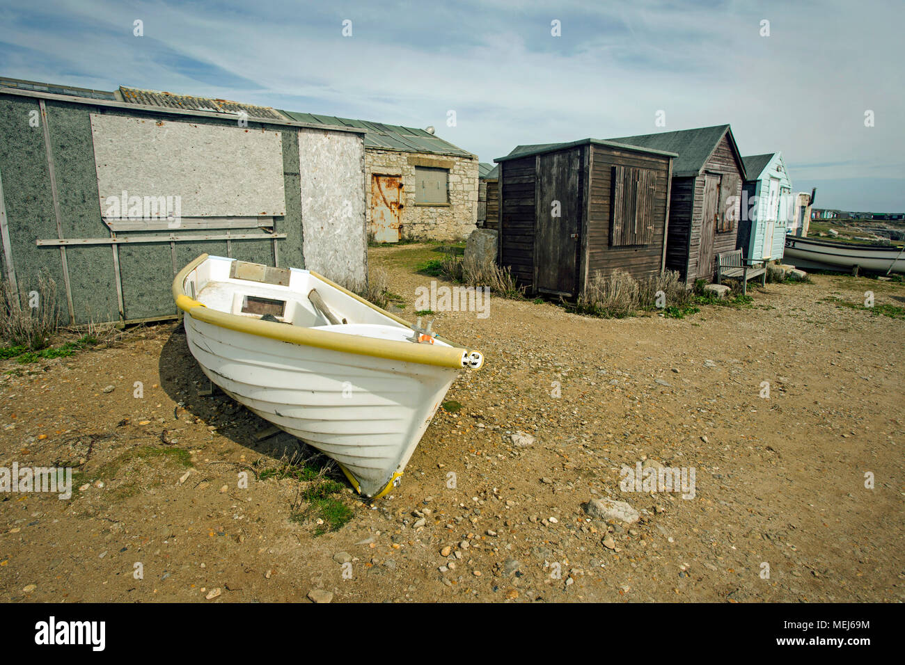 A white rowing boat on the shore by ramshackle wooden huts used by fishing personnel. - Stock Image