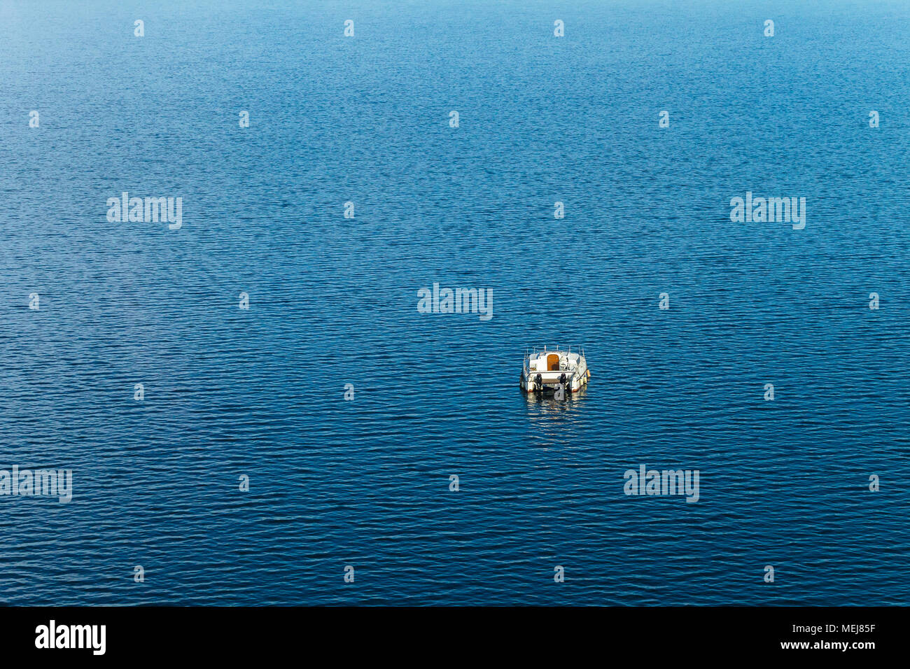 Boat alone on dam waters birds-eye flying photo - Stock Image